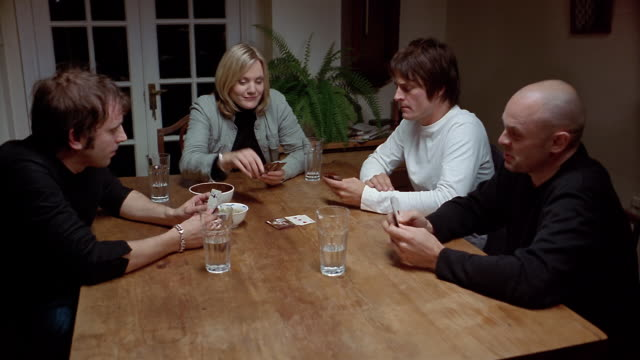 high angle medium shot dolly shot three men and a woman playing cards at table - carte da gioco video stock e b–roll