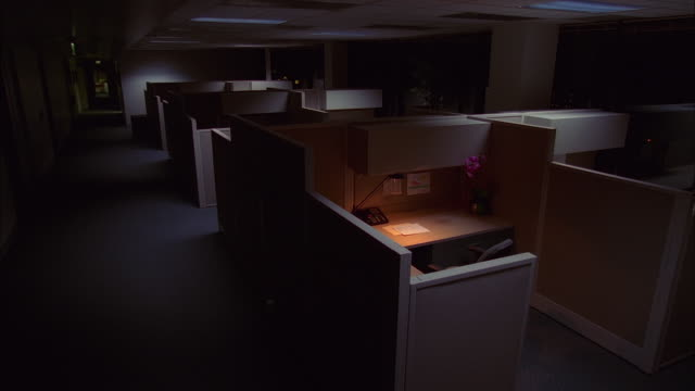 High angle medium shot empty office cubicles at night