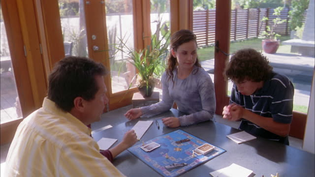 high angle medium shot family playing board game at table - 30 39 years stock videos & royalty-free footage
