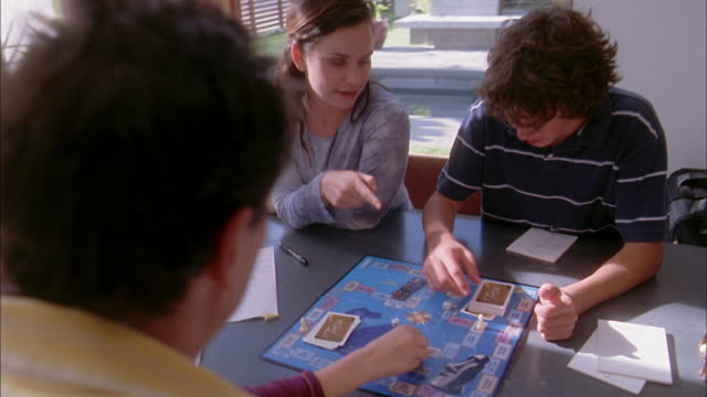 High angle medium shot family playing board game at table