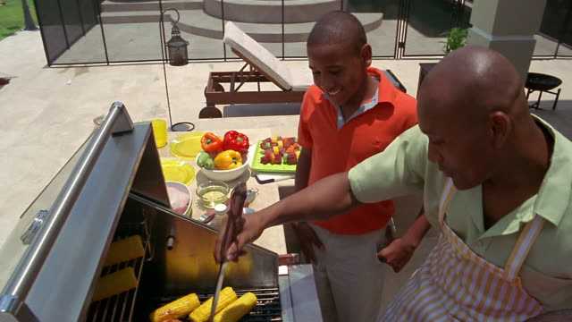 stockvideo's en b-roll-footage met high angle medium shot father instructing sons how to barbecue over grill - haarborstel