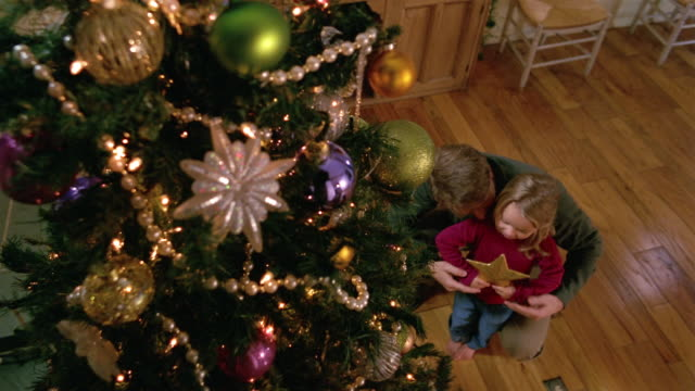 high angle medium shot father lifting daughter up / tilt up daughter placing star on top of christmas tree - decorating the christmas tree stock videos & royalty-free footage