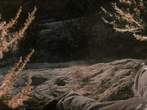 vidéos et rushes de 1978 high angle medium shot feet and legs of man trying to get hold on crumbling cliff - 1978