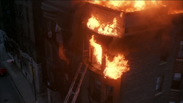 high angle medium shot fire burning on top floor of apartment building with ladder leading up to fire escape - fire escape stock videos & royalty-free footage