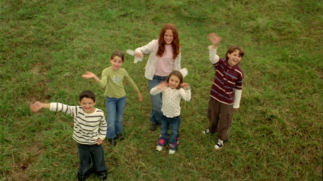 High angle medium shot five kids standing in field looking up and waving / jumping up + down
