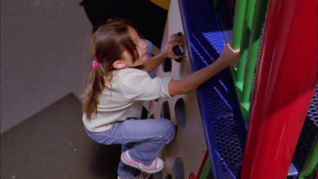 high angle medium shot girl and boy climbing up climbing wall on playground - climbing wall stock videos & royalty-free footage