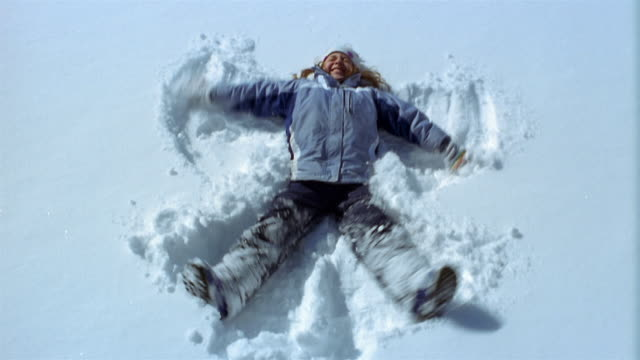 High angle medium shot girl falling back onto snow / making snow angel / Vermont