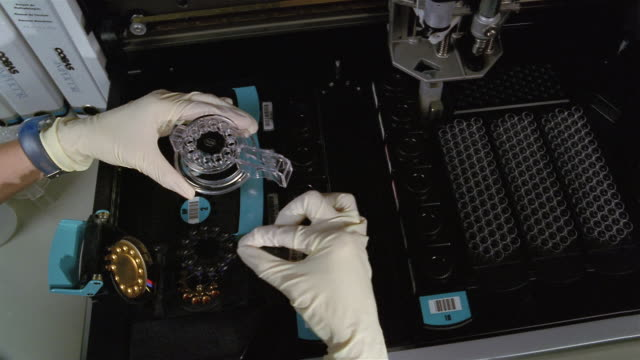 high angle medium shot gloved hand placing nucleic acid sample into dna purification system - dna test stock videos and b-roll footage