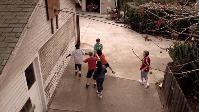 vídeos de stock, filmes e b-roll de high angle medium shot kids playing basketball in driveway with hoop on garage - entrada para carros
