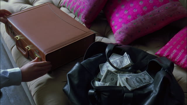 high angle medium shot leather bag filled with stacks of money / man opening briefcase also filled w/ money - 5ドル米国紙幣点の映像素材/bロール