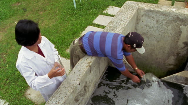high angle medium shot male and female worker checking water quality at waste treatment plant / manila, philippines - sewage treatment plant stock videos & royalty-free footage