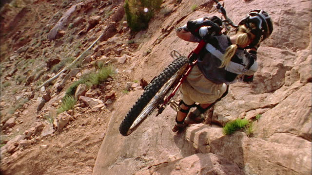 high angle medium shot man carrying mountain bike - moab utah stock-videos und b-roll-filmmaterial