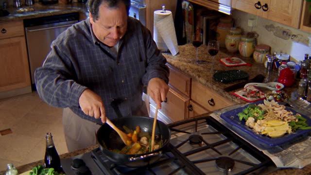 vidéos et rushes de high angle medium shot man in kitchen stirring food in wok / dancing and shaking wooden utensils - cooking pan