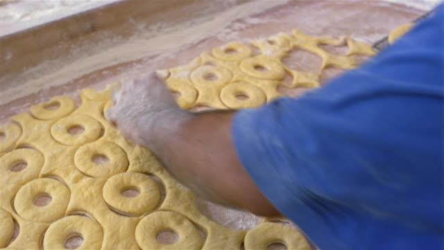 high angle medium shot man removing doughnuts cutouts from dough / placing them on baking sheet in doughnut bakery - baking sheet stock videos & royalty-free footage