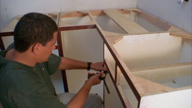 vidéos et rushes de high angle medium shot man securing cabinets with vice - bricolage