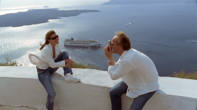High angle medium shot man taking picture of woman on terrace / cruise ship in bay in background / Santorini, Greece