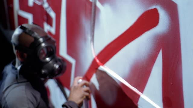 high angle medium shot man wearing mask spray painting wall - graffito stock-videos und b-roll-filmmaterial