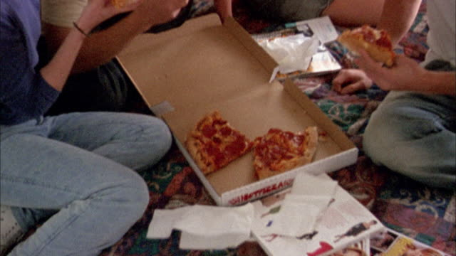 vidéos et rushes de high angle medium shot men and women eating pizza from carton on bed - bed