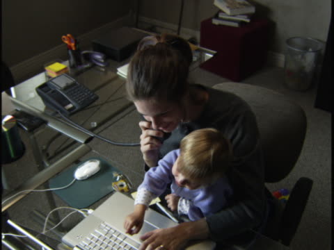high angle medium shot of a woman in her home office with a child on her lap as she uses the phone