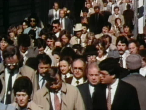 1984 high angle medium shot office workers walking on crowded sidewalk during rush hour / AUDIO