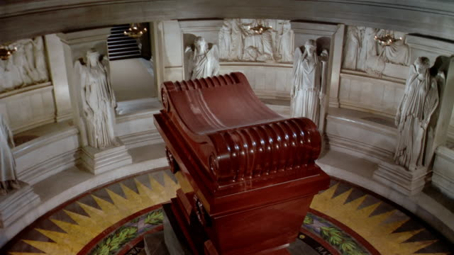 High angle medium shot pan around coffin in Napoleon's tomb surrounded by statues / Paris, France