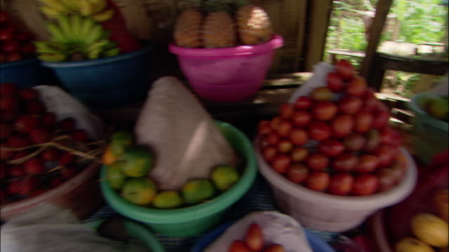 high angle medium shot pan bowls of various kinds of fruit at stand in ubud / bali, indonesia - ubud stock videos & royalty-free footage