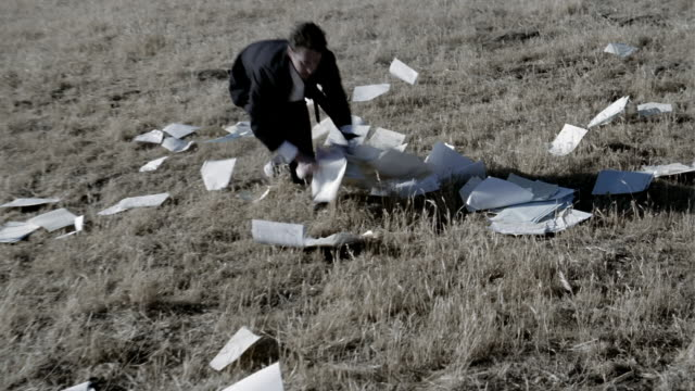 high angle medium shot pan businessman running around field and picking up papers - chaos stock-videos und b-roll-filmmaterial