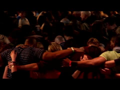 high angle medium shot pan crowd of people in group hug engaged in prayer/ man laughing/ crowd lifting heads/ london, england - praying stock videos & royalty-free footage