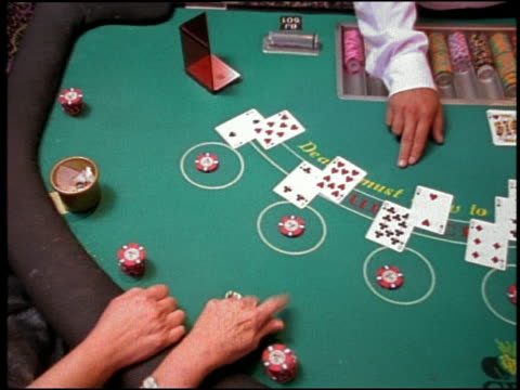 high angle medium shot pan dealer and players at blackjack table - blackjack video stock e b–roll