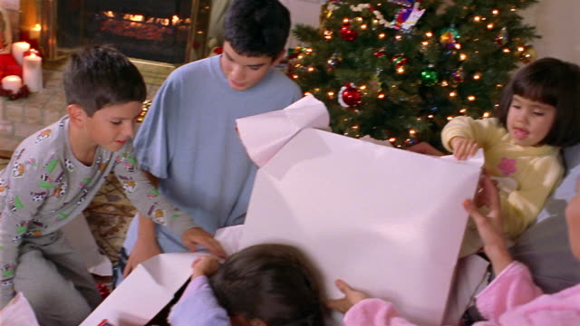 High angle medium shot pan family opening Christmas presents / girls unwrapping stuffed animals and hugging them