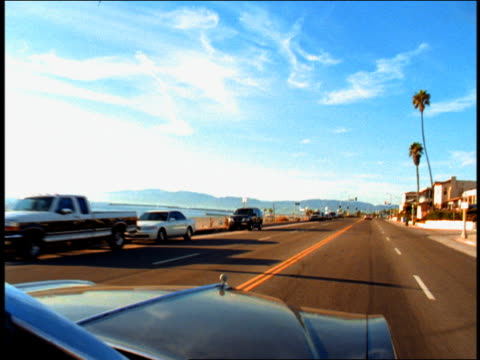 vídeos de stock, filmes e b-roll de high angle medium shot pan from coastal road to young man driving convertible on coast with couple in backseat / california - passear sem destino