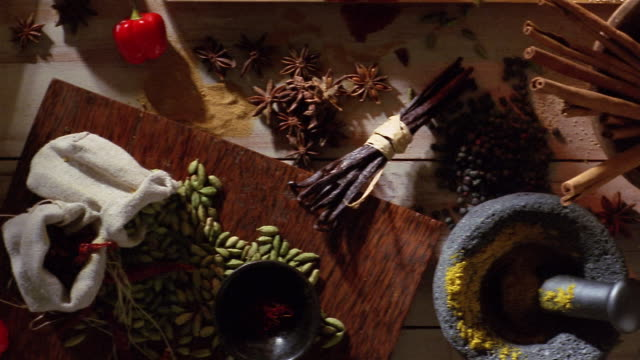 high angle medium shot pan herbs and spices arranged on a tabletop - cinnamon stock videos & royalty-free footage