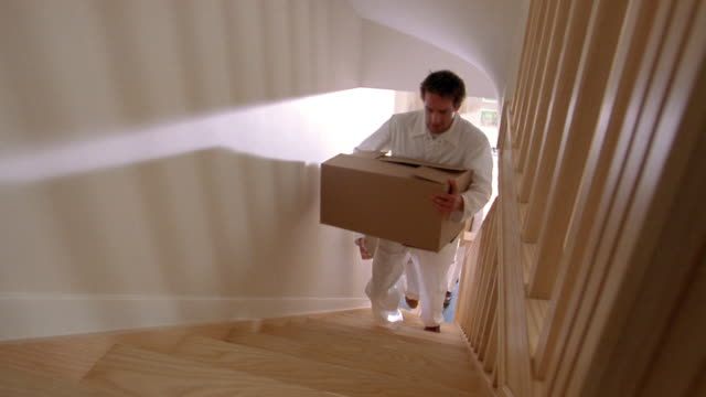 High angle medium shot pan movers carrying boxes up two flights of stairs in new home