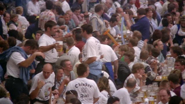 high angle medium shot pan revelers drinking / waiter carrying tray in pavilion at oktoberfest / munich, germany - betrunken stock-videos und b-roll-filmmaterial