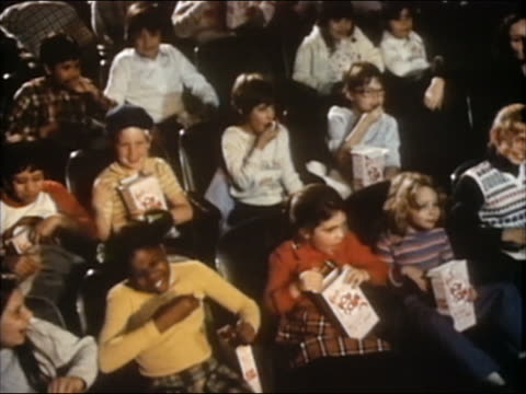 1985 high angle medium shot preteens watching movie in a theater / holding popcorn boxes