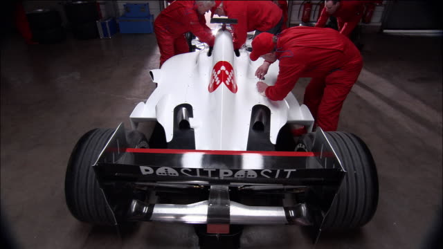 High angle medium shot rear view of Formula One race car being serviced by mechanics