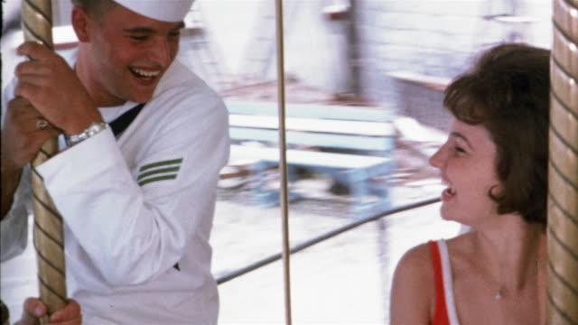 vidéos et rushes de 1965 high angle medium shot sailor and young woman smiling + flirting on merry-go-round - marinière