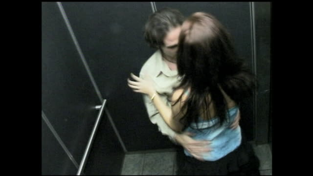stockvideo's en b-roll-footage met high angle medium shot security camera point of view couple kissing passionately and taking off clothes in elevator / los angeles - jong koppel