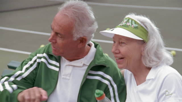 High angle medium shot senior couple sitting near tennis court, talking and laughing / woman kissing man on cheek