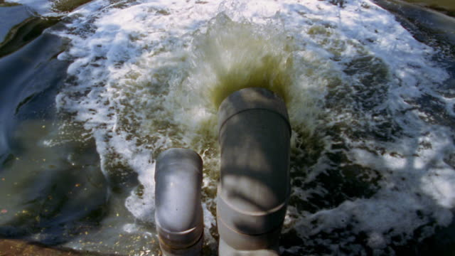 high angle medium shot sewer pipe spraying into water / jakarta - sewage treatment plant stock videos & royalty-free footage