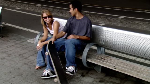 high angle medium shot skateboarder skates up to girl and sits next to her on bench / talking / skating away / nyc - next to stock videos and b-roll footage