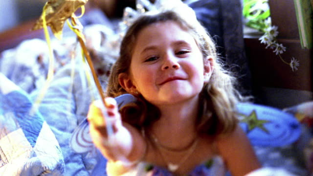 high angle medium shot small girl pointing magic wand - magician stock videos & royalty-free footage