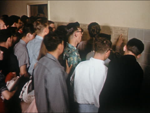 1956 high angle medium shot teenagers in high school hallway crowding around post on bulletin board - notice board stock videos and b-roll footage
