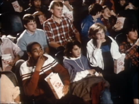1985 high angle medium shot teens sitting in a movie theater and eating popcorn - popcorn stock-videos und b-roll-filmmaterial