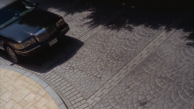 high angle medium shot tiled driveway / limousine pulling up driveway and parking - limousine luxuswagen stock-videos und b-roll-filmmaterial