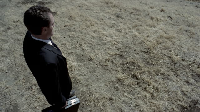 vidéos et rushes de high angle medium shot tilt up businessman spinning around and throwing briefcase / raising his arms - objet manufacturé