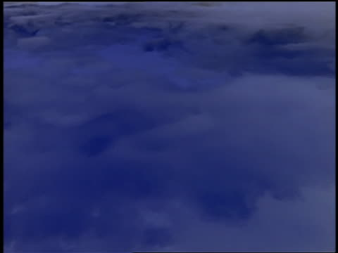 High angle medium shot time lapse sea of blue and white clouds moving fast