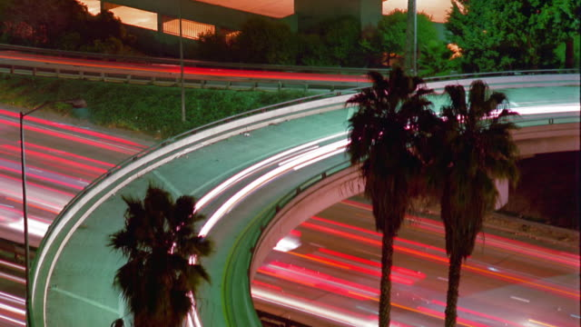 vídeos y material grabado en eventos de stock de high angle medium shot time lapse traffic on overpass and highway with palm trees / los angeles, california - 1985