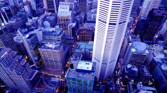 High angle medium shot time lapse traffic on streets below downtown city skyscrapers / Sydney