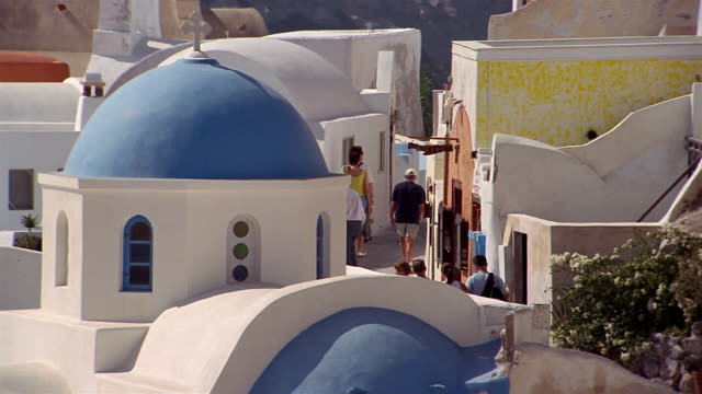 high angle medium shot tourists walking past blue church dome in the village of ia / santorini, greece - oia santorini stock videos & royalty-free footage